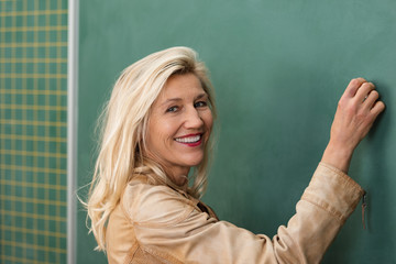 lächelnde lehrerin schreibt an die tafel