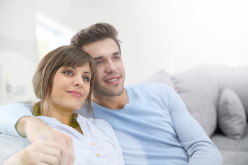Young couple relaxing in sofa, looking towards the future