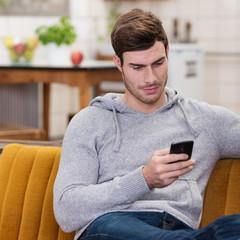 junger mann schaut zu hause auf sein mobiltelefon