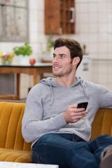 junger mann mit handy auf seinem sofa