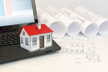 Small house on laptop near scrolls of architectural drawings
