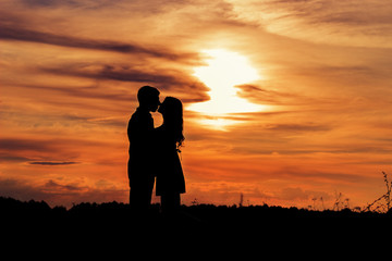 loving happy couple kissing at sunset in a field