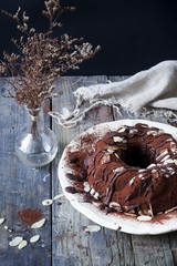 ring-shaped cake covered with cocoa powder and almond slices