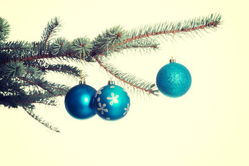 Three christmas balls hanging on a twig.