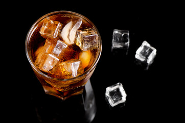 glass of cola with ice on black table