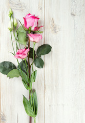 eustoma and roses on wooden surface