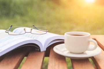 Close up glasses on book and Coffee cup on the table in the morn