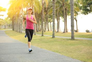 woman runner athlete running at tropical park