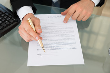 Businessman With Pen And Contract Document At Desk
