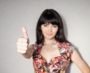 successful woman holds his thumb up.