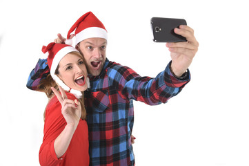 young romantic couple in love taking santa hats Christmas selfie