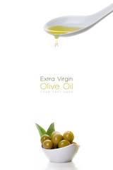 Virgin olive oil dripping from spoon over bowl of olives