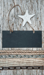 Chalkboard with chain and seashell on the old wood