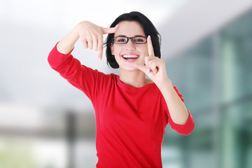 Happy girl with face in frame of palms