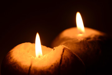 Two burning candles on a black background