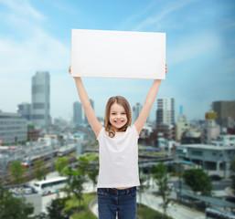 smiling little girl holding blank white board
