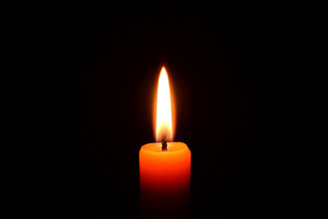 Orange candle burning on a black background