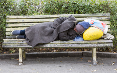 Homeless man sleeping on a bench Fotomurales