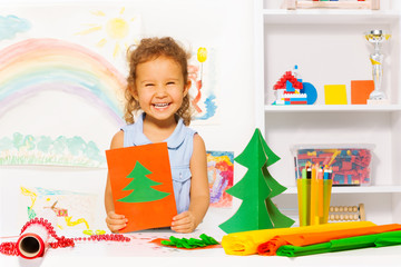 Laughing girl holding carton card with Xmas tree