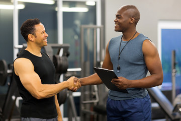 african gym trainer handshaking with mid age client