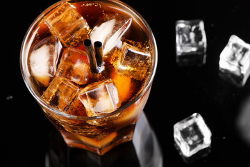 A full glass of cola with ice cubes