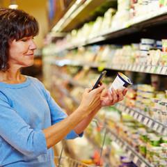 Frau mit Smartphone scannt Barcode im Supermarkt