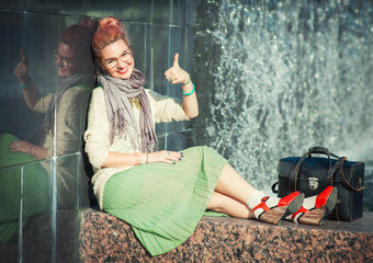 Beautiful girl in vintage clothing showing thumbs up gesture
