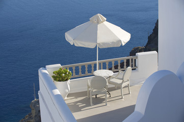 Two chairs under umbrella with the view. Oia, Santorini, Greece