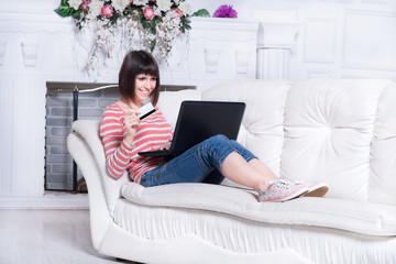 young girl sitting on a white sofa with a laptop and credit card