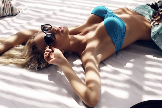 sexy girl in bikini and sunglasses relaxing on summer beach
