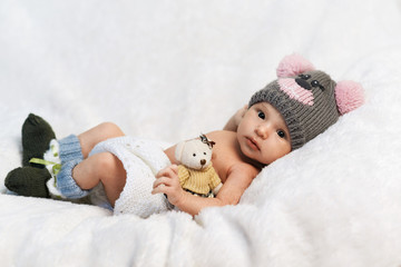 newborn baby with teddy bear in a knitted hat