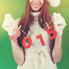 Cute young Christmas woman holding 2015 number