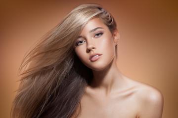 Wall Mural - Beautiful Blond Girl. Healthy Long Hair. Brown Background