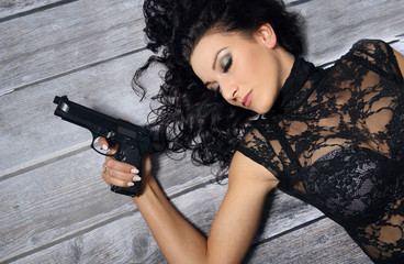 Bad brunette girl with gun