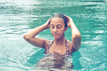 Young Asian woman meditating in a pool