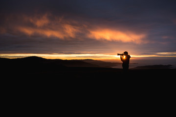 silhouetted photographer in sunset sky