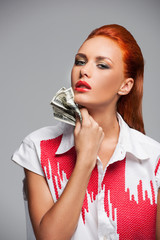 Young hot woman with dollars on grey background.