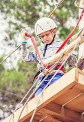 Boy in safe equipment on the rope track
