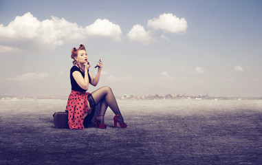 woman paints her lips sitting on a suitcase outdoors.