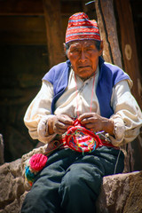 Old men knitting at taquile island in puno peru.