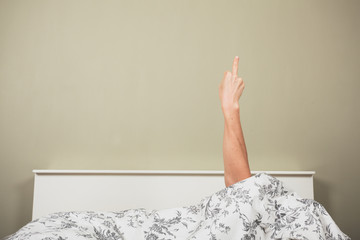 Woman in bed displaying obscene gesture