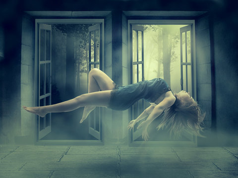 Levitating young woman in her house