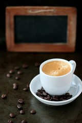 Coffee cup and coffee beans with blank chalk board