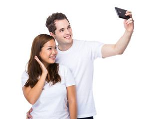 Asian woman and caucasian man take selfie together