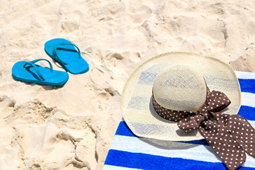 Straw hat, towel and flip flops on  sand beach