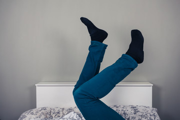 Man in bed with his legs raised