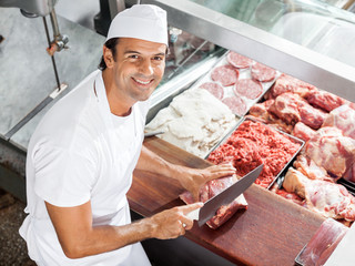 Smiling Butcher Cutting Meat At Counter
