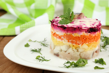 Russian herring salad on plate on wooden table background