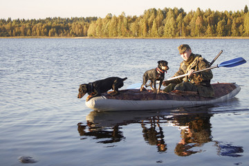 The hunter floats in the boat with two dogs