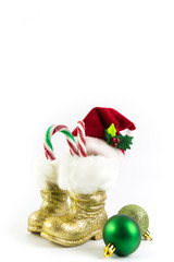 Santas golden boots and red hat with Christmas balls isolated